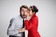 年轻人告诉闲话对他的妇女同事在办公室 免版税库存照片