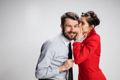 年轻人告诉闲话对他的妇女同事在办公室 库存图片