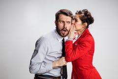 年轻人告诉闲话对他的妇女同事在办公室 免版税库存图片