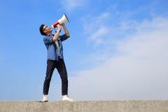 年轻人呼喊扩音机 免版税库存照片