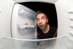 人和一个空的冰箱 库存照片