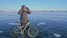 人和他的自行车在冰 他站立和神色在美好的日落 骑自行车者在灰色下来夹克打扮 免版税图库摄影