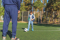 人和儿子一起踢橄榄球 免版税库存图片
