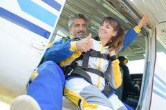 人和夫人保持平衡做纵排skydive 免版税库存照片