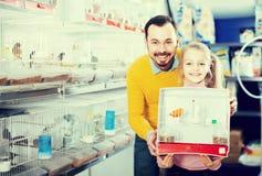 人和女儿买了您的宠物的一只笼子 图库摄影