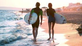 人和女孩冲浪者一对年轻夫妇沿在保温潜水服的海滩走 在拿着冲浪板的手上 查找 影视素材
