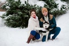 人和女孩在有狗的冬天森林里走 免版税库存照片