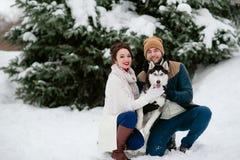 人和女孩在有狗的冬天森林里走 库存照片