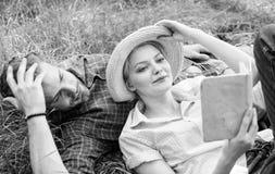 人和女孩在草看书放置 家庭享受休闲有诗歌或文学书草背景 ?? 库存照片