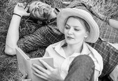 人和女孩在草阅读书放置 夫妇知己在浪漫日期 在爱的夫妇花费休闲看书  免版税库存照片