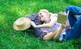 人和女孩在获得的绿草放置乐趣 在爱的夫妇花费休闲阅读书 夫妇知己在浪漫日期 免版税库存图片