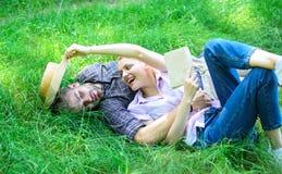 人和女孩在获得的绿草放置乐趣 在爱的夫妇花费休闲阅读书 浪漫夫妇学生享用 免版税库存图片