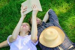 人和女孩在获得的草放置乐趣 在爱的夫妇花费休闲阅读书 夫妇知己在浪漫日期 免版税库存照片