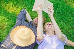 人和女孩在获得的草放置乐趣 在爱的夫妇花费休闲阅读书 夫妇知己在浪漫日期 库存图片