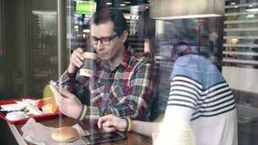 人和女孩有LGBT镯子标志的,在咖啡馆、一杯咖啡和一个手机 股票录像