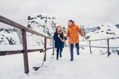 人和女孩步行和获得乐趣在森林里在冬天 库存图片