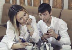 从人和女孩的夫妇有茶时光在咖啡馆和看在智能手机absorbedly 免版税库存图片