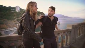 人和女孩皮夹克的,站立在俯视海和峭壁的阳台 股票视频