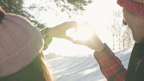 人和女孩结合,显示心脏标志阳光火光 股票录像