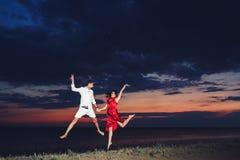 人和女孩跳握手的乐趣反对美好的日落的背景 库存图片