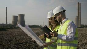 人和女性分析和检查计划项目的工程师工友在气体能量工厂附近计划- 股票视频