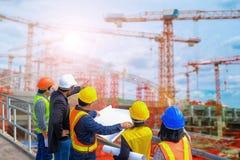 人和妇女会谈与工程师和监督员站立读图纸工地工作 免版税库存图片