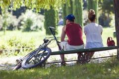 年轻人和妇女坐一条长凳在公园在晴朗的夏天 免版税库存图片