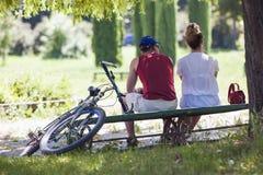 年轻人和妇女坐一条长凳在公园在晴朗的夏天 免版税库存照片
