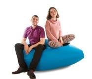 年轻人和妇女坐蓝色装豆子小布袋沙发 免版税库存照片