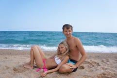 年轻人和妇女有休息在海 免版税库存图片