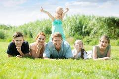 年轻人和妇女有在公园的四个孩子的 库存照片