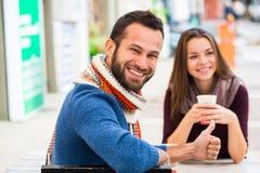 人和妇女饮用的茶或者咖啡 野餐 饮料温暖在凉快的天气 愉快的加上咖啡杯在秋天停放 男孩庭院女孩亲吻的爱情小说 免版税图库摄影