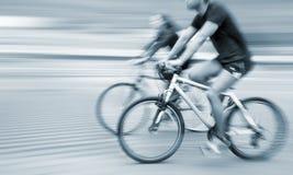 年轻人和妇女骑马在城市街道上骑自行车 库存照片