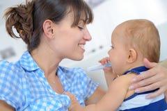 人和婴孩有温度计的 免版税库存照片
