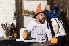 人和孩子与疯狂的面孔在巫婆帽子 免版税库存图片