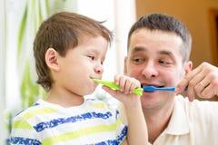 人和孩子男孩掠过的牙在卫生间里 免版税库存图片