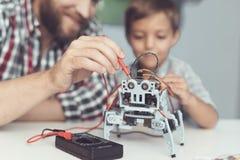 人和小男孩测量机器人` s表现 他们使用一个数字式多用电表 库存图片