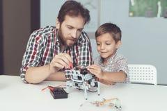 人和小男孩测量机器人` s表现 他们使用一个数字式多用电表 库存照片