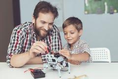 人和小男孩测量机器人` s表现 他们使用一个数字式多用电表 图库摄影