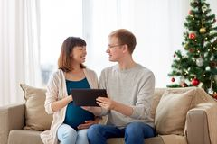 人和怀孕的妻子有片剂个人计算机的在圣诞节 免版税库存图片