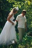 人和新娘在绿色公园在一个夏天 免版税库存照片
