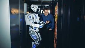 人和机器人检查导线在数据中心,关闭  股票视频