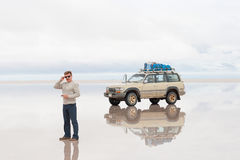 人和汽车在湖撒拉族de Uyuni 免版税库存图片