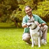 人和狗在公园 免版税库存图片