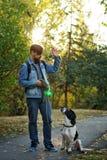 人和狗在秋天公园 免版税图库摄影