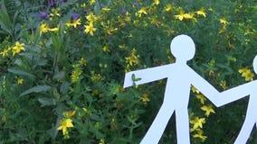 人和环境的概念 人的图由纸制成在草 全景从人的慢动作照相机 股票视频