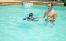 人和男孩戏剧在游泳场的水中 库存照片