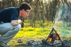 人和篝火在春天火的森林煤炭 日落 免版税库存图片