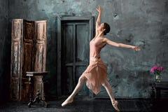 年轻人和难以置信地美丽的芭蕾舞女演员是摆在和跳舞在一个黑演播室 免版税库存照片