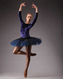年轻人和难以置信地美丽的芭蕾舞女演员蓝色成套装备的是摆在和跳舞在演播室 古典芭蕾艺术 在一条腿上 库存照片